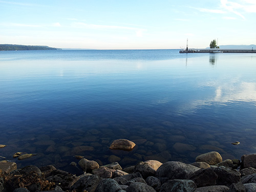 Jönköping pier and rocky beach, blue water reflecting the sky. Photo Vaida Staberg.