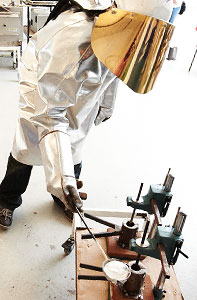 Person in lab coat melting aluminium
