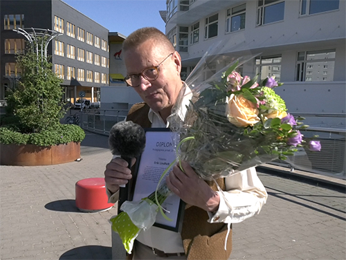 Erik Lindfelt with flowers and diploma